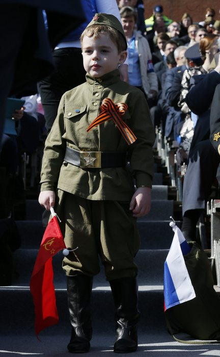 epa04739416 A child dressed in Red Army soldiers style uniform at the Red Square to attend a Victory Day military parade in Moscow, Russia, 09 May 2015. The Victory Day parade on 09 May 2015 marks the 70th anniversary since the capitulation of Nazi Germany.  EPA/SERGEI ILNITSKY