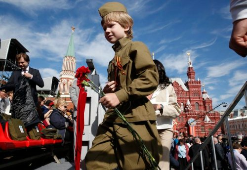 epaselect epa04739386 A child dressed in Red Army soldiers style uniform carry flowers as he arrives at the Red Square to attend a Victory Day military parade in Moscow, Russia, 09 May 2015. The Victory Day parade on 09 May 2015 marks the 70th anniversary since the capitulation of Nazi Germany.  EPA/SERGEI ILNITSKY
